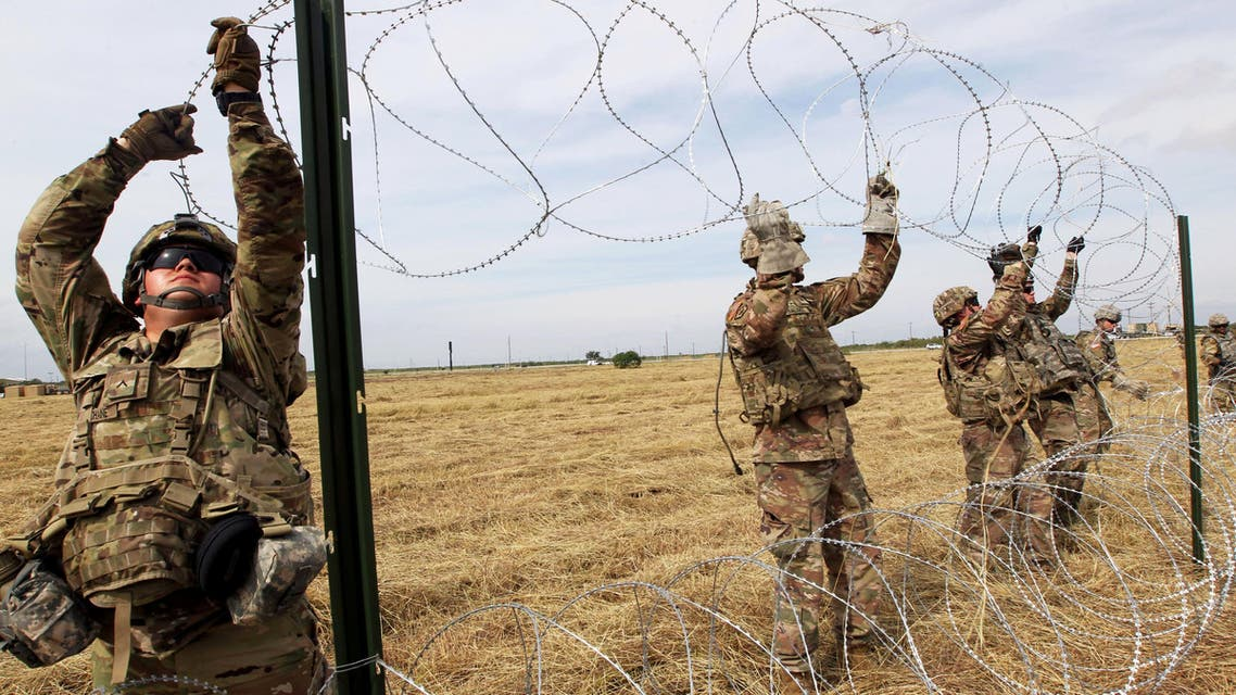 U.S. Army soldiers from Ft. Riley, Kansas, put up barbed wire fence for an encampment to be used by the military near the U.S. Mexico border in Donna, Texas, U.S., November 4, 2018. REUTERS/Delcia Lopez TPX IMAGES OF THE DAY