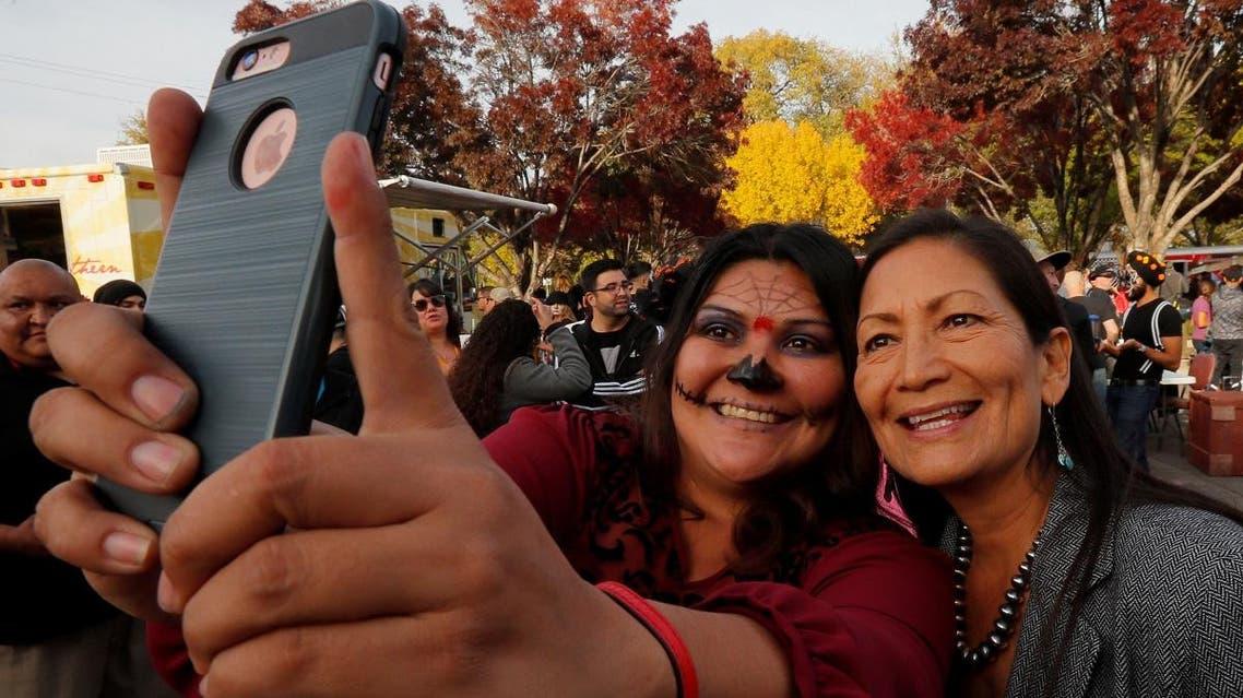 U.S. Democratic Congressional candidate Deb Haaland poses for a selfie with a supporter at the Dia de los Muertos parade in Albuquerque. (Reuters)