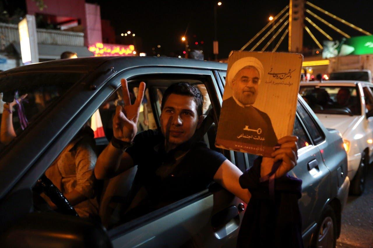 رجل إيراني يحمل صورة للرئيس حسن روحاني خلال الاحتفالات في طهران بعد التوصل إلى الاتفاق النووي.