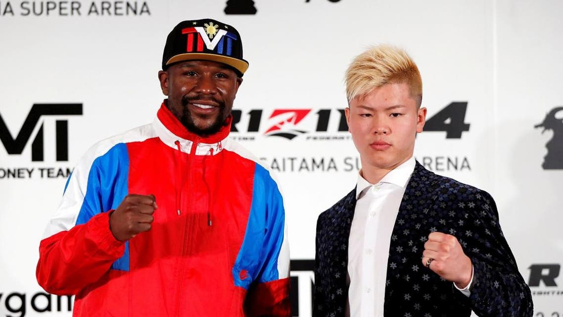 Boxer Floyd Mayweather Jr. of the U.S. poses for a photograph with his opponent Tenshin Nasukawa during a news conference in Tokyo. (Reuters)