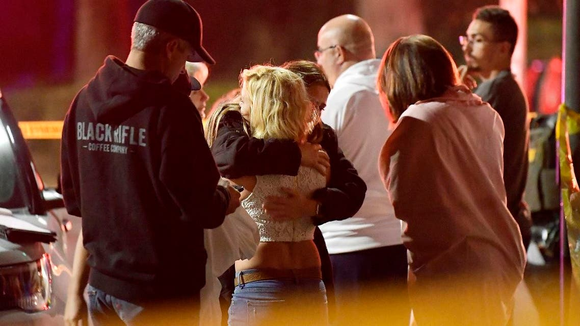 People comfort each other as they stand near the scene Thursday, on November 8, 2018, in Thousand Oaks, California, where a gunman opened fire Wednesday inside a country dance bar. (AP)