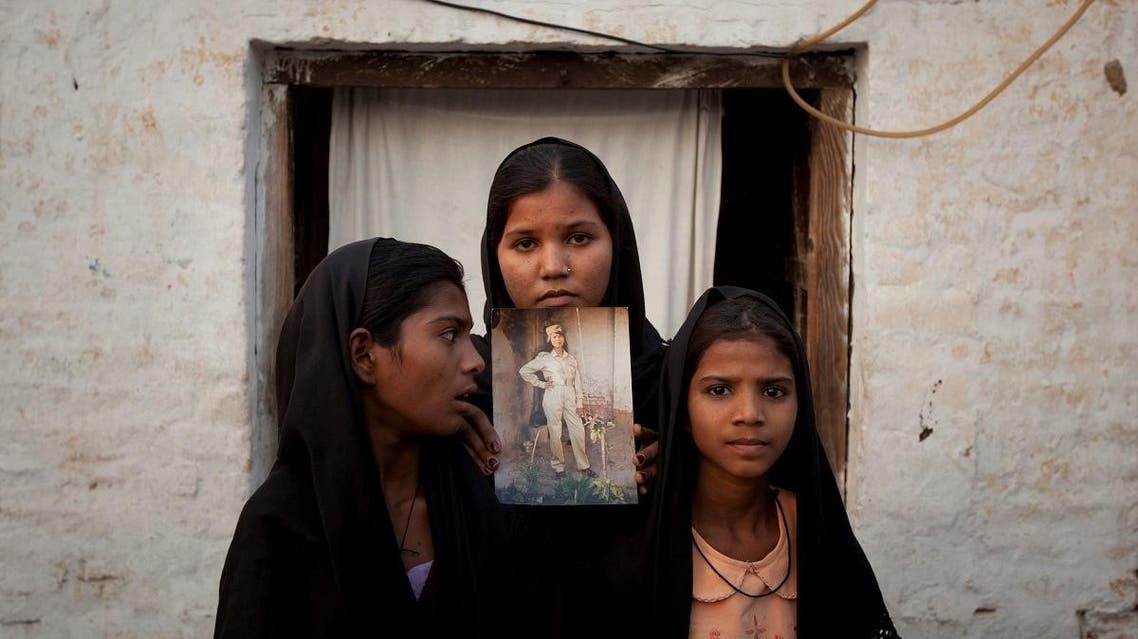 The daughters of Pakistani Christian woman Asia Bibi pose with an image of their mother while standing outside their residence in Sheikhupura Pakistan. (Reuters)