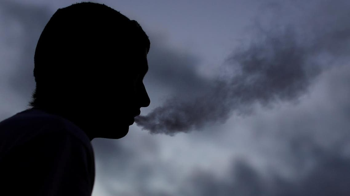 A young man smokes a Suorin Drop electronic cigarette in this picture illustration taken September 14, 2018. (Reuters)