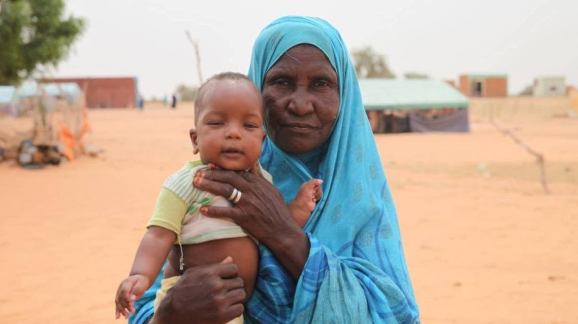 Salma Mint Mahmoud poses with a grandchild in the commune of Dar El Barka, Mauritania, October 20, 2018. (Thomson Reuters Foundation/Nellie Peyton)