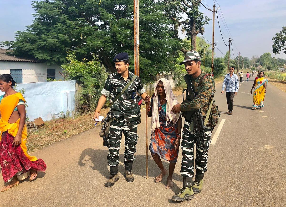 Indian security personnel assist an elderly woman to join a line of voters at a polling station in Sukma in Chhattisgarh state on November 12, 2018. (AFP)