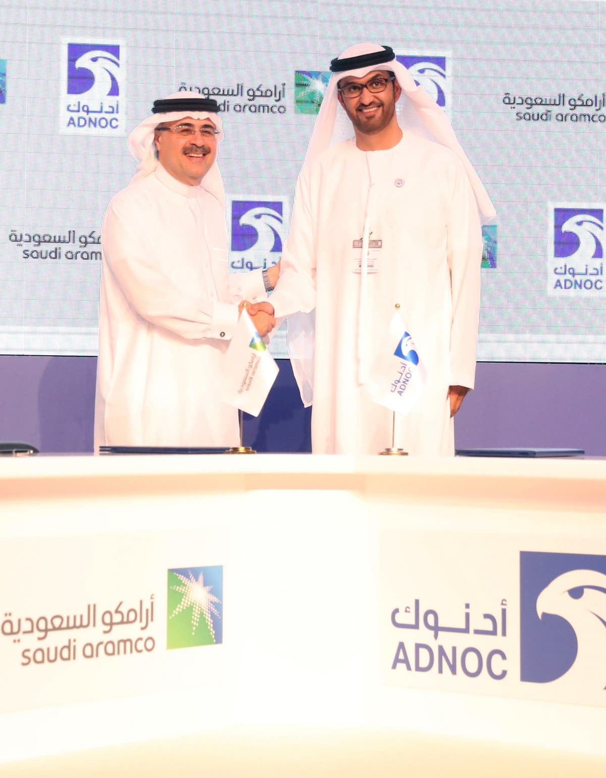 Sultan Ahmed al-Jaber (R), the director general and CEO of the Abu Dhabi National Oil Company (ADNOC), shakes hands with Saudi Aramco CEO Amin Nasser after signing a cooperation deal in Abu Dhabi on November 12, 2018.  (AFP)