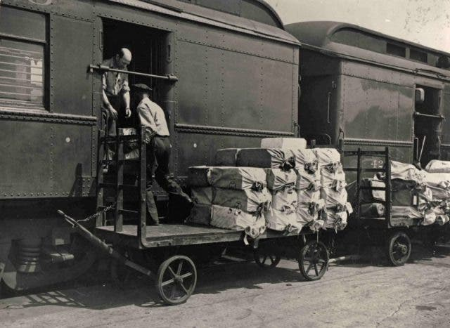 صورة لعملية شحن عدد من الطرود البريدية داخل احدى عربات القطار المخصص للبريد