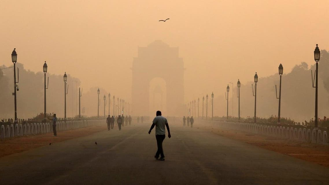 A man walks in front of the India Gate shrouded in smog in New Delhi. (Reuters)
