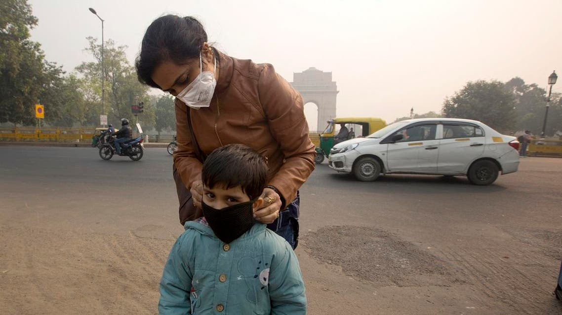 An Indian mother puts a mask to her son a day after Diwali festival in New Delhi, India. (AP)