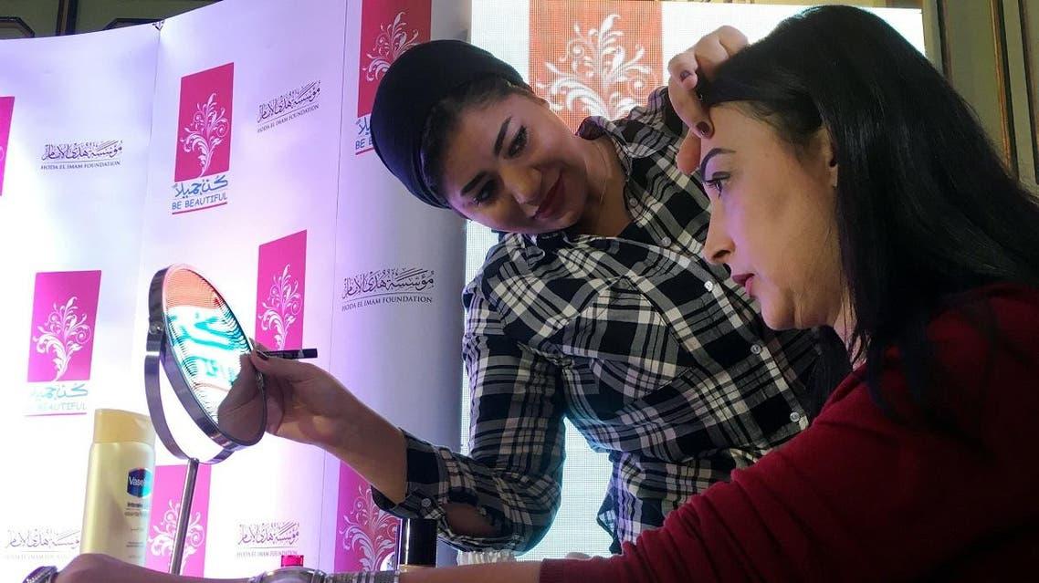 Kout Ibrahim shows cancer patient Merhan Khalil how to put on makeup at Cairo's Marriott Hotel. (Reuters)