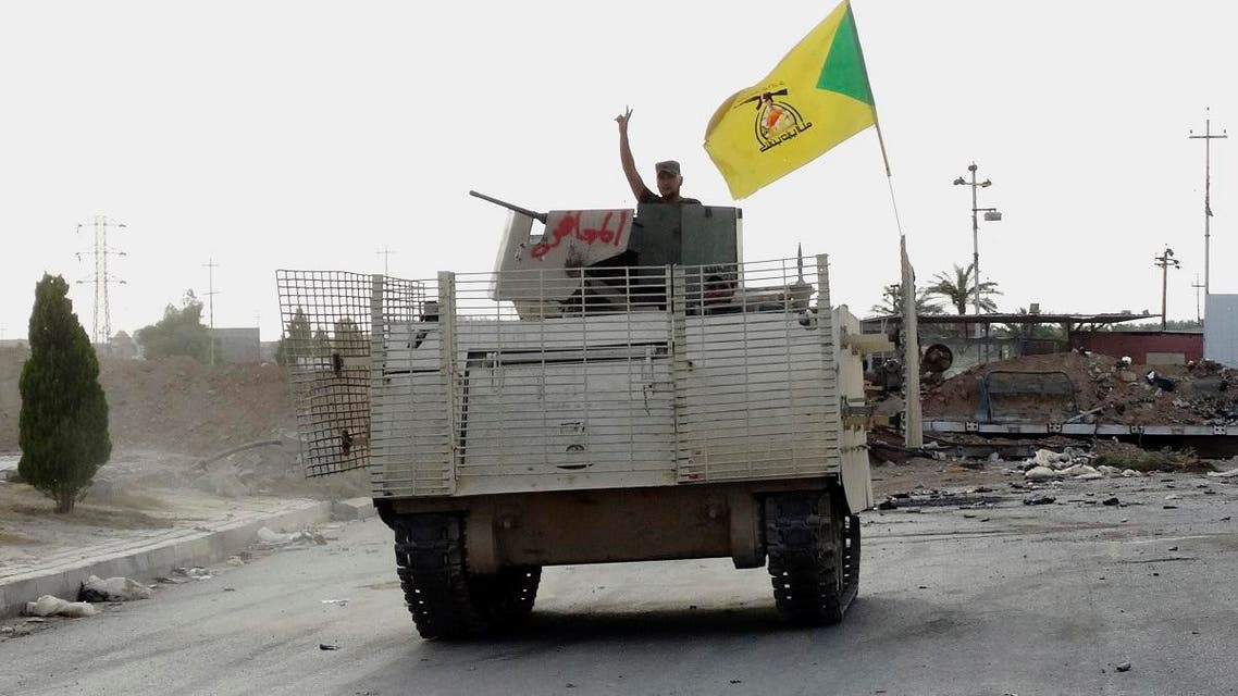 In this Wednesday, May 27, 2015 photo, a fighter on an armored vehicle belonging to the Shiite Hezbollah Brigade waves a v-sign as he patrols after regaining control from the Islamic State group in eastern Husaybah town, 8 kilometers (5 miles) east of Ramadi, Iraq. (AP Photo)