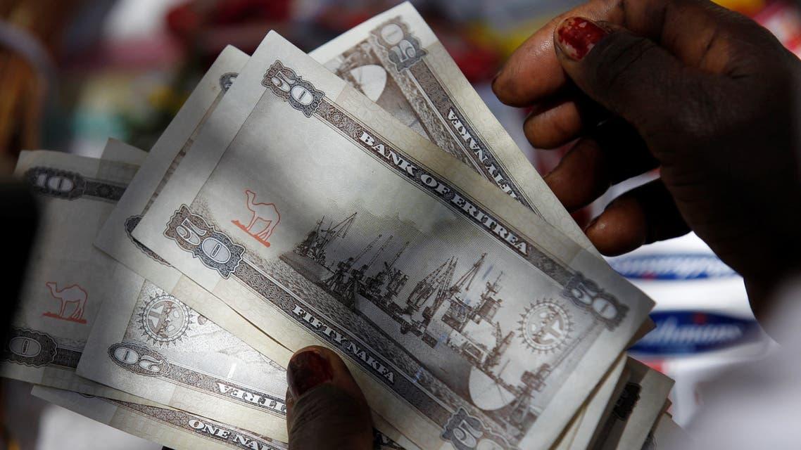"A vendor counts Eritrean ""Nakfa"" bank notes in downtown Asmara, Eritrea in this photo taken on February 21, 2016. Picture taken February 21, 2016. REUTERS/Thomas Mukoya"