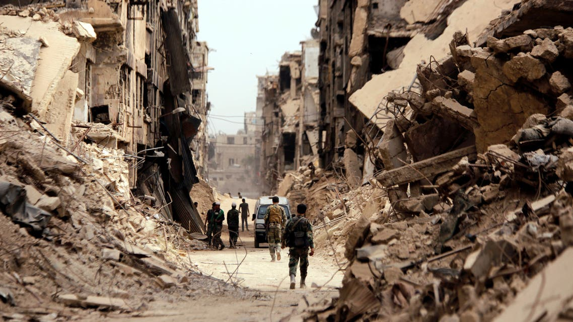 FILE PHOTO: Soldiers walk past damaged buildings in the Yarmouk Palestinian camp in Damascus, Syria May 22, 2018. REUTERS/Omar Sanadiki - RC18889192B0/File Photo