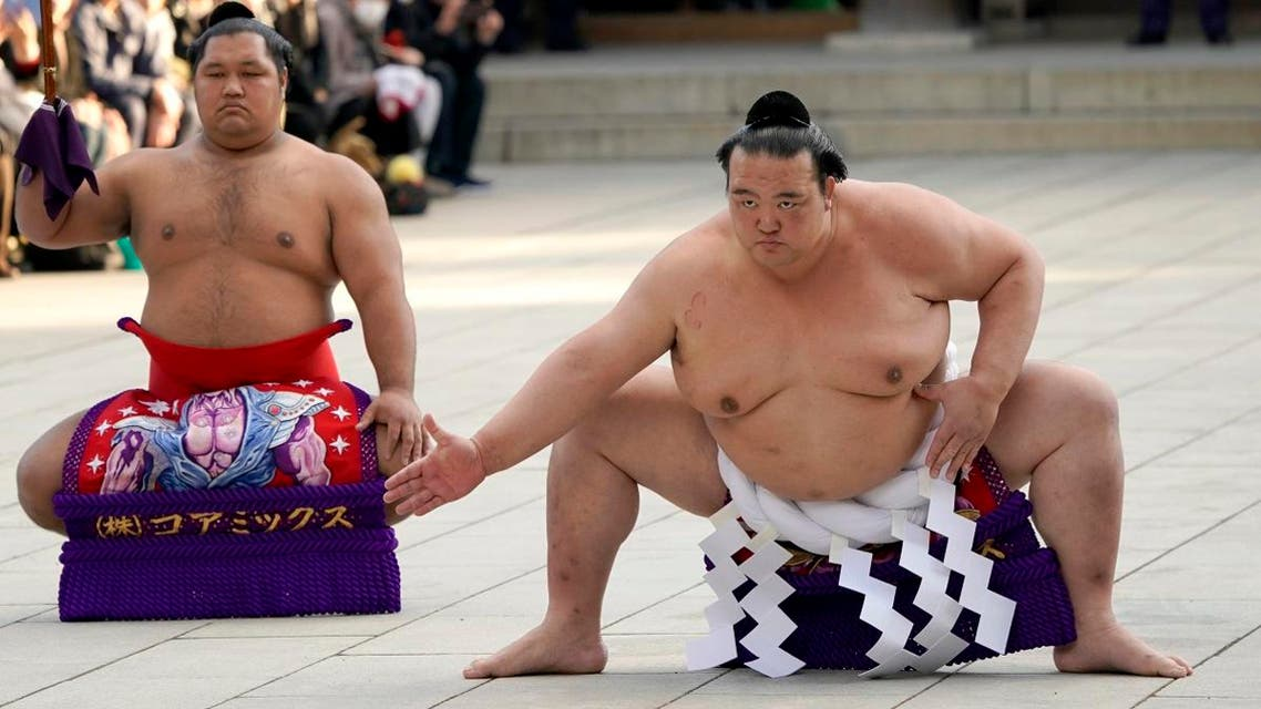 Sumo grand champion Kisenosato, right, of Japan performs his ring entry form with sward-holder Shohozan at the Meiji Shrine in Tokyo, Tuesday, Jan. 9, 2018. (AP)