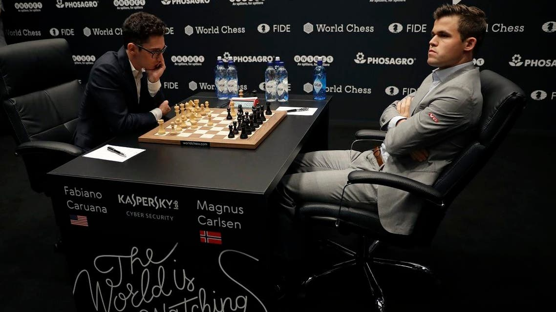 Reigning chess world champion Magnus Carlsen, right, from Norway, plays Italian-American challenger Fabiano Caruana in the first five minutes of round three of their World Chess Championship Match in London, Monday, Nov. 12, 2018. (AP)