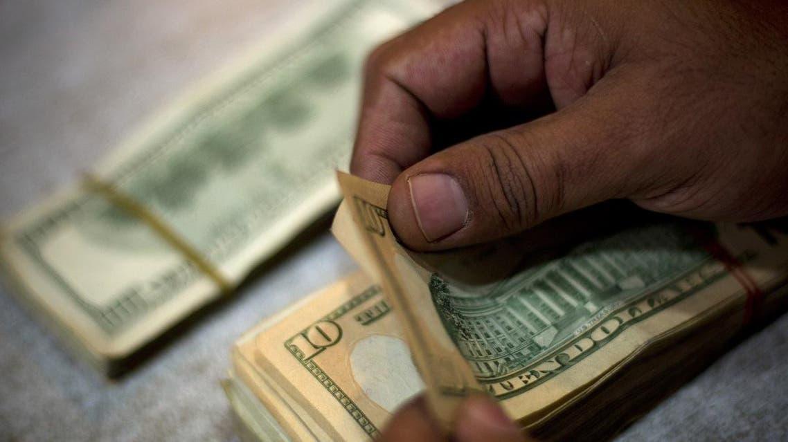 A Pakistani money changer counts dollar bills at his shop in Islamabad, Pakistan. (AP)