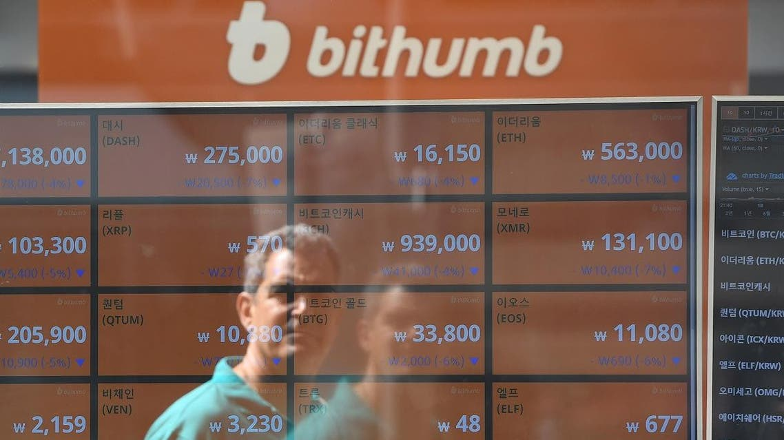 A man is reflected on a screen showing exchange rates of cryptocurrencies at Bithumb virtual currency exchange in Seoul. (AFP)