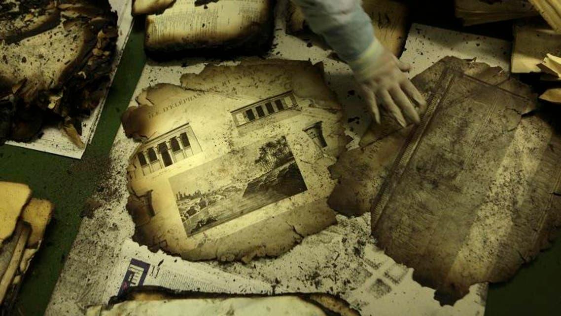 """An Egyptian book restoration official arranges burnt pages of the original ancient copy identified as """"Le Description de L'Egypt"""" ap"""