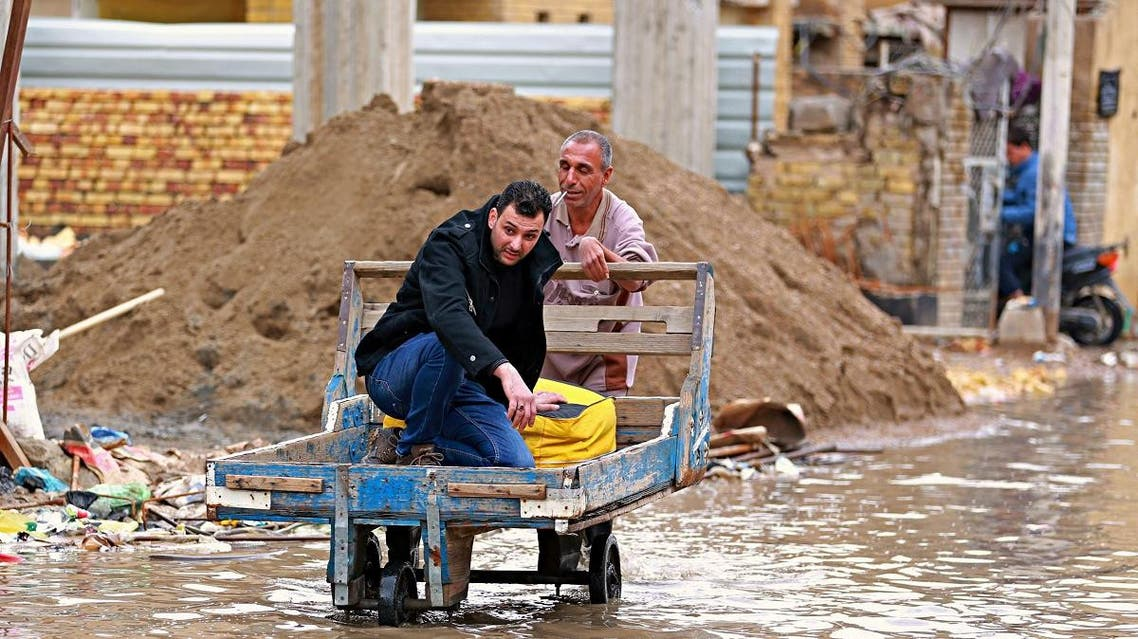 File photo of man who hired a pushcart to navigate a flooded street after a heavy rainfall in Iraq. (AP)