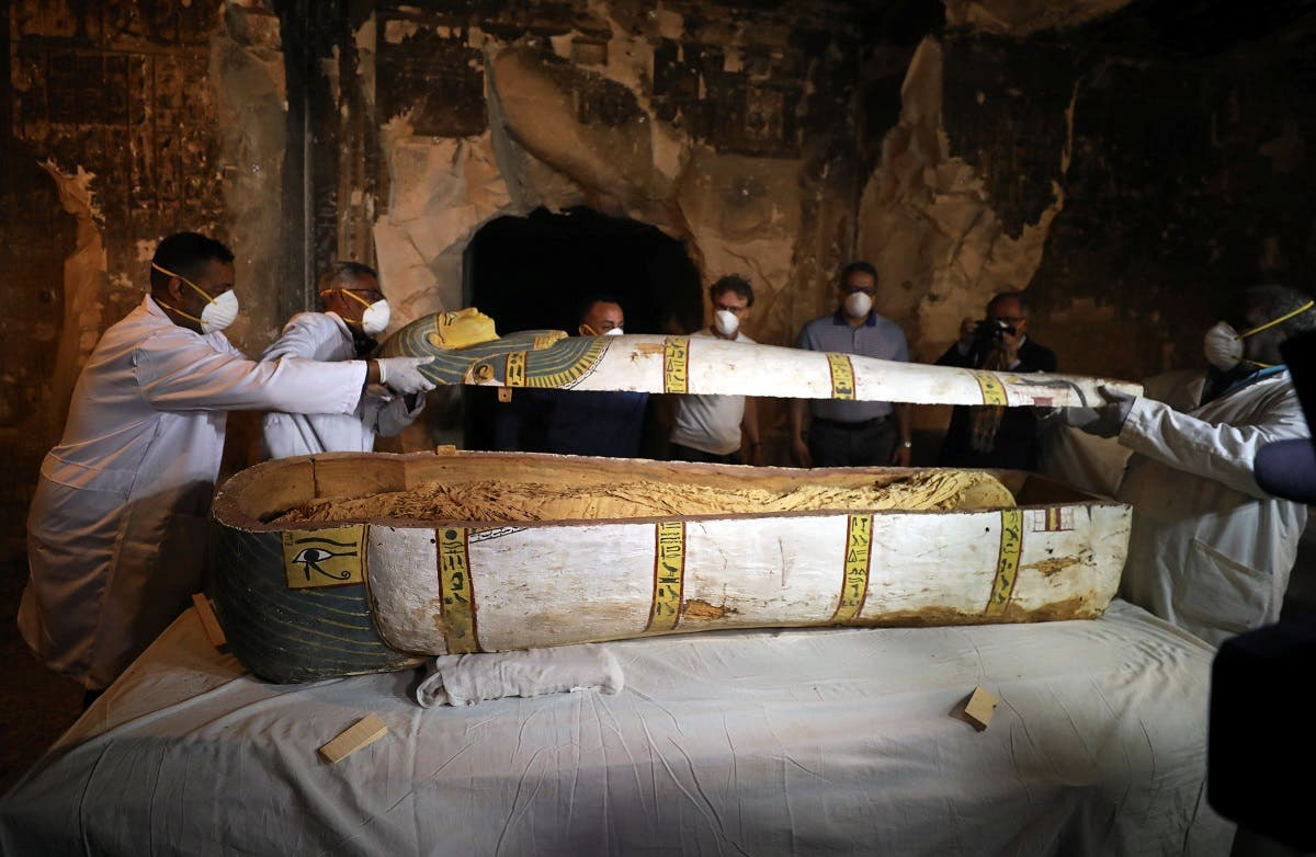 Archaeologists remove the cover of an intact sarcophagus inside the tomb TT33 in Luxor. (Reuters)
