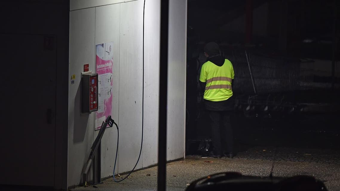 A man wearing a yellow vest and reportedly wielding a grenade, which could be tear gas, stands as police carry out an intervention at the car wash station of the Espace Anjou shopping centre in Angers, western France, on November 23, 2018. (AFP)