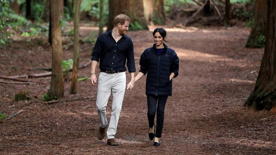 Britain's Prince Harry and Meghan, Duchess of Sussex walk through a Redwoods forest in Rotorua, New Zealand, Wednesday. (Reuters)