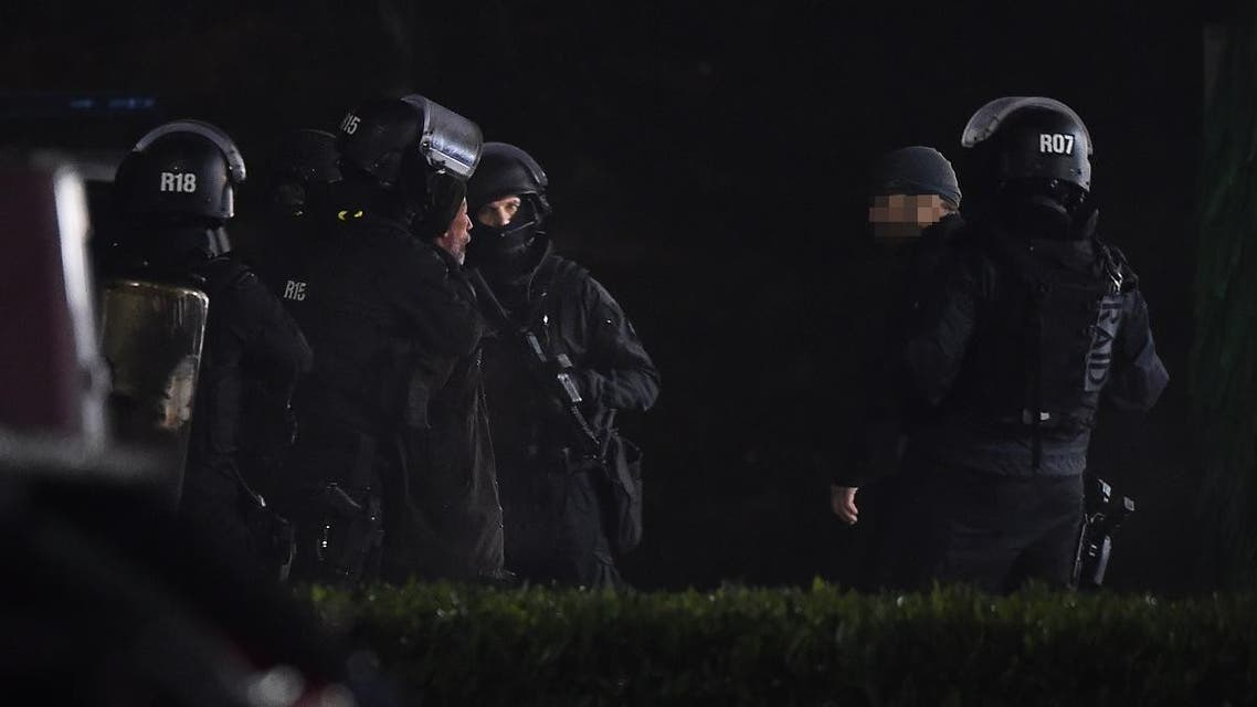Members of the RAID elite police unit detain a man (2nd L) who was wearing a yellow vest and wielding a grenade, which could be tear gas, after he surrendered to police at the car wash station of the Espace Anjou shopping centre in Angers, western France, on November 23, 2018. (AFP)