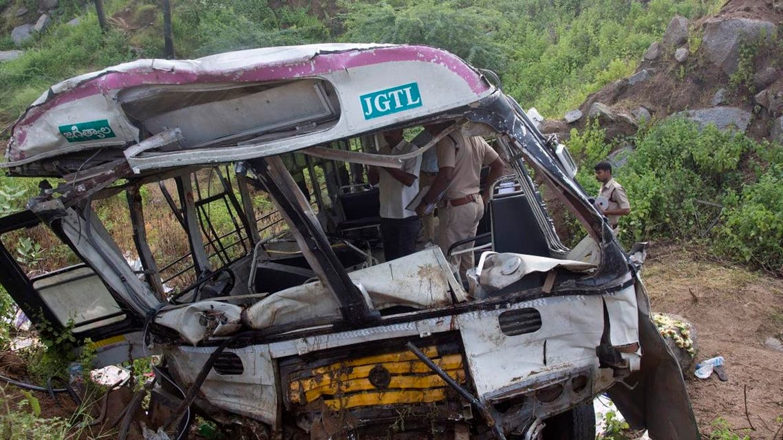 Government officials and policemen inspect a bus that fell into a gorge in Jagtiyal district, in the southern Indian state of Telangana, Wednesday, Sept. 12, 2018.