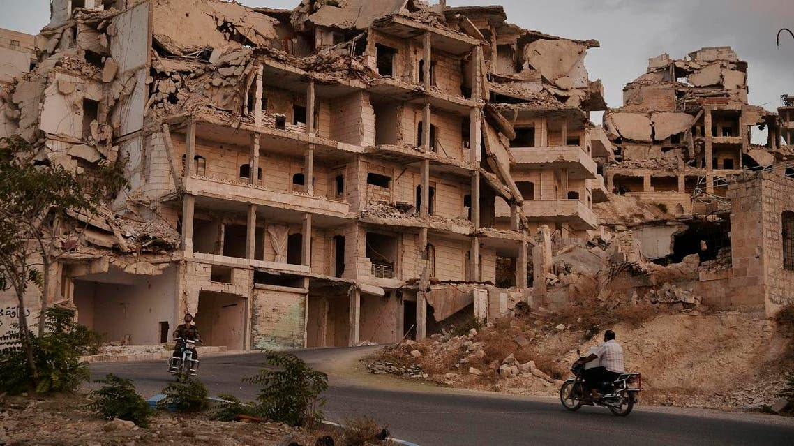 In this Sept. 20, 2018, file photo, motor cycles ride past buildings destroyed during the fighting in the northern town of Ariha in Idlib province, Syria. (AP)