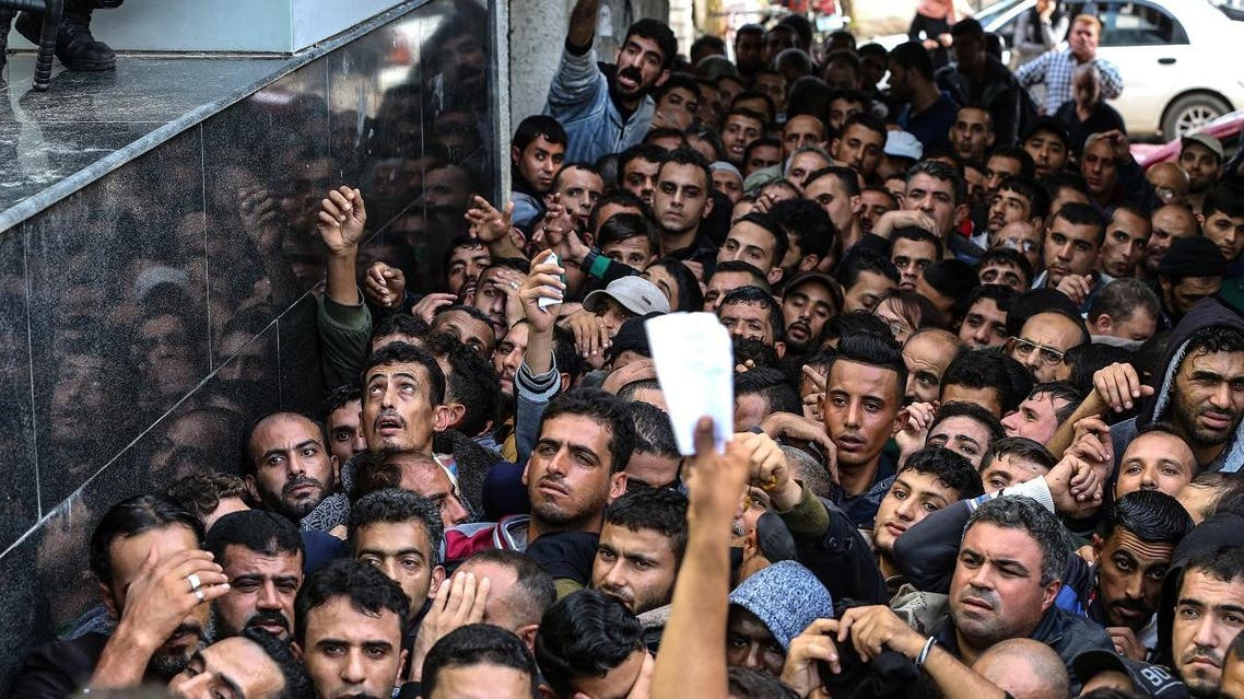 Palestinians gather to receive money aid from Qatar government for poor families in Gaza city on Nov. 10. (AFP)