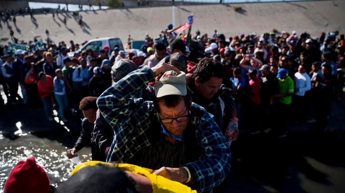 Migrants cross the river at the Mexico-U.S. border after pushing past a line of Mexican police at the Chaparral crossing in Tijuana, Mexico, Sunday, Nov. 25, 2018. (AP)