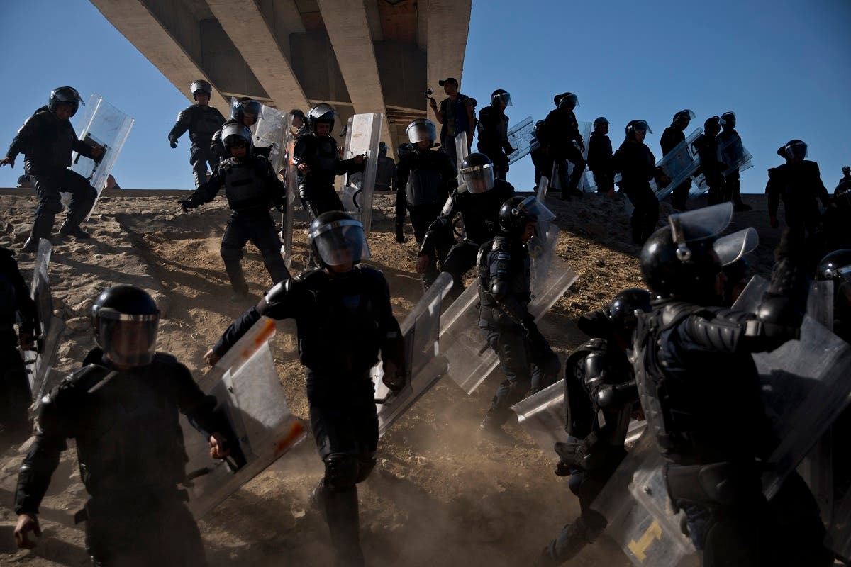 Mexican police run as they try to keep migrants from getting past the Chaparral border crossing in Tijuana, Mexico, Sunday, Nov. 25, 2018. (AP)