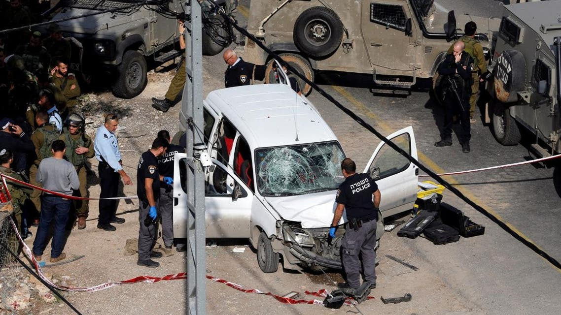 Israeli policemen inspect the scene of a car ramming attack near Hebron, in the occupied West Bank. (Reuters)