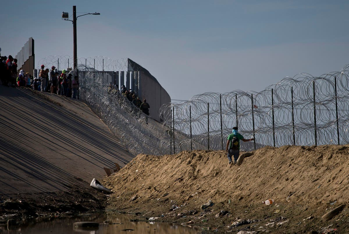 Migrants, top left, speak with U.S. border agents standing on the other side of razor wire near the Chaparral border crossing, seen from Tijuana, Mexico, Sunday, Nov. 25. (AP)