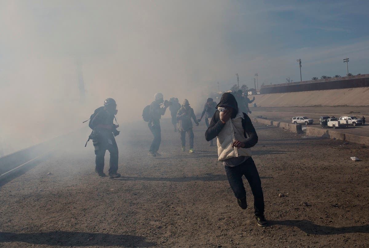 Migrants run from tear gas launched by U.S. agents, amid photojournalists covering the Mexico-U.S. border, after a group of migrants got past Mexican police at the Chaparral crossing in Tijuana, Mexico, Sunday, Nov. 25. (AP)