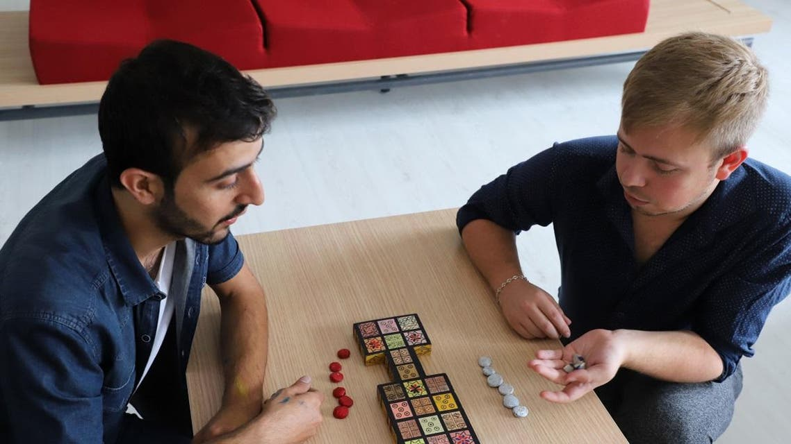 Iraqi artist Hoshmand Mofaq and British archaeologist Ashley Barlow (R) play an ancient board game, known as the Royal Game of Ur, in the northern Iraqi city of Raniey. (AFP)