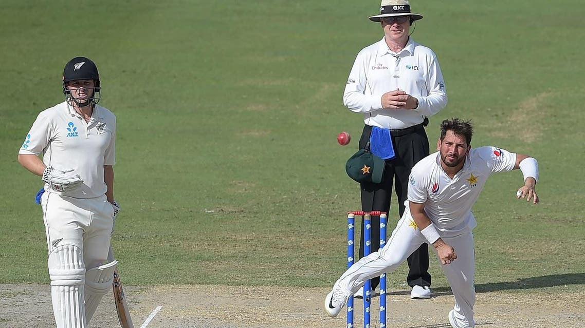 Yasir Shah (R) delivers the ball as New Zealand batsman Henry Nicholls (L) looks on during the fourth day of the second Test cricket match between Pakistan and New Zealand at the Dubai International Stadium in Dubai on November 27, 2018. (AFP)
