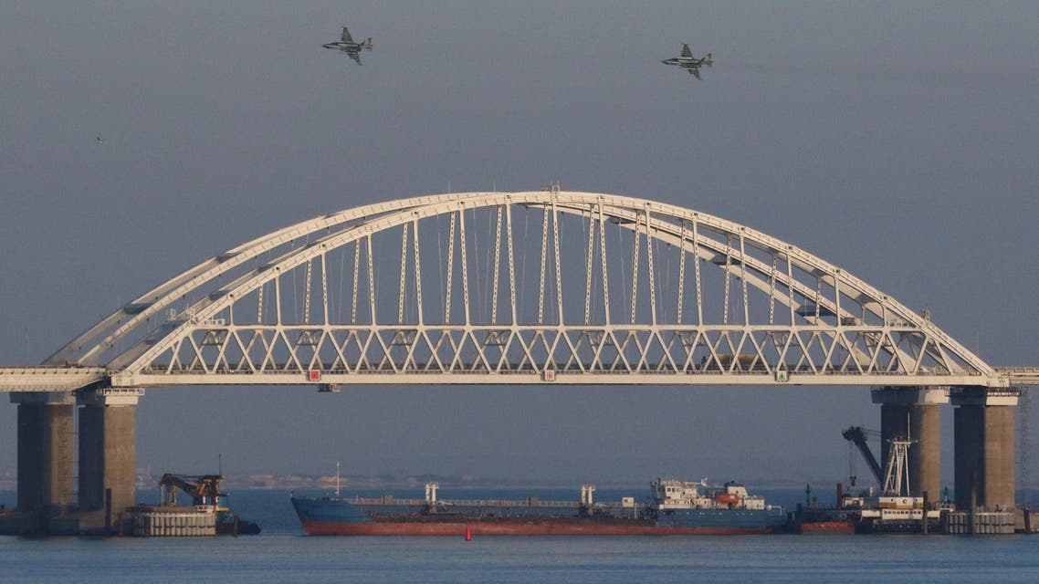 FILE PHOTO: Russian jet fighters fly over a bridge connecting the Russian mainland with the Crimean Peninsula with a cargo ship beneath it after three Ukrainian navy vessels were stopped by Russia from entering the Sea of Azov via the Kerch Strait in the Black Sea, Crimea November 25, 2018. REUTERS/Pavel Rebrov/File Photo