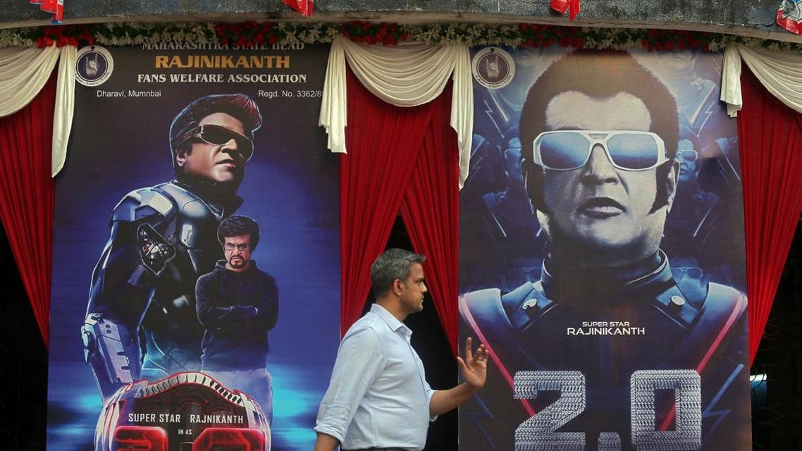 """A man walks past a cinema decorated with posters of Tamil film star Rajinikanth's new movie """"2.0"""" on the eve of its release. (Reuters)"""