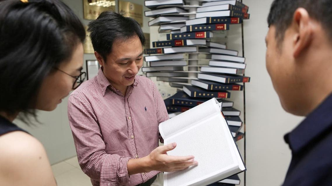 "Scientist He Jiankui shows ""The Human Genome"", a book he edited, at his company Direct Genomics in Shenzhen. (Reuters)"