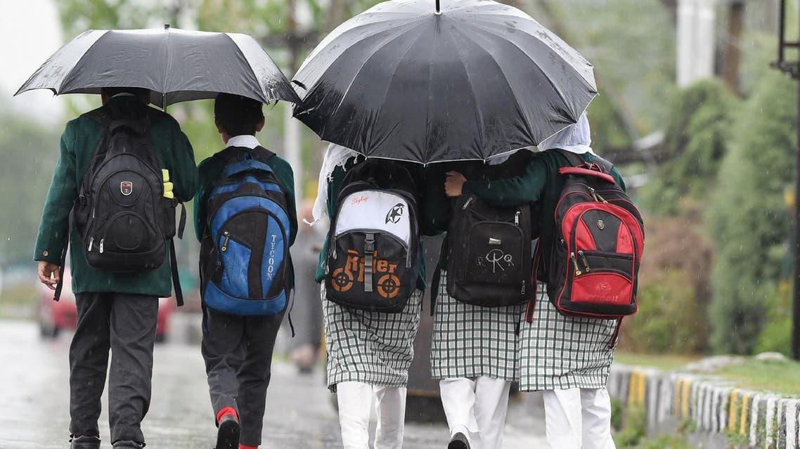Indian Kashmiri schoolchildren walk toward school during rainfall in Srinagar on April 10, 2018. (AFP)
