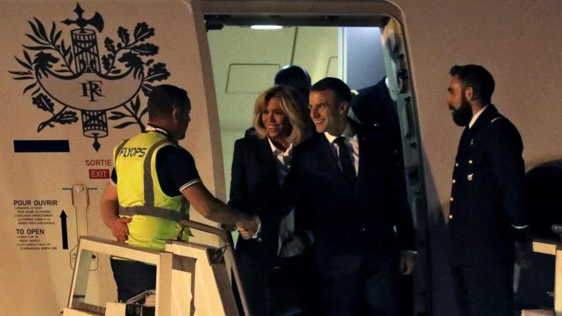 French President Emmanuel Macron (2nd R) next to First Lady Brigitte Macron, shakes hands with a crew member before leaving the plane, upon arrival at Ezeiza airport, in Buenos Aires province, on November 28, 2018. (AFP)
