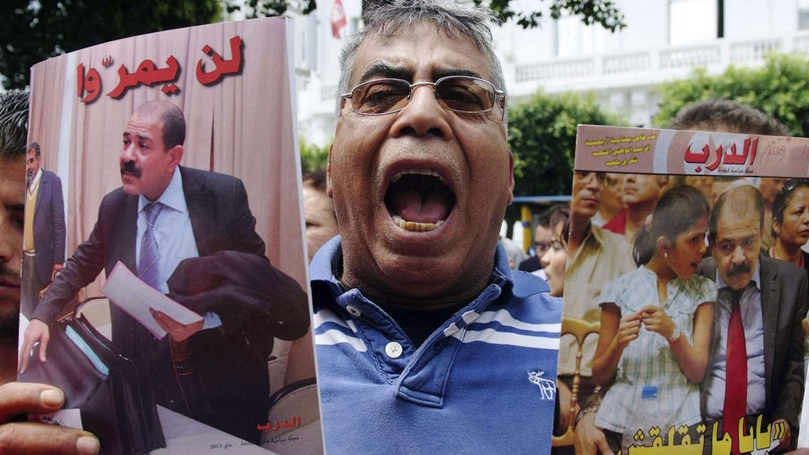 A protester shouts slogans as he holds portraits of the late Tunisian opposition leader Chokri Belaid, who was assassinated in 2013. (File photo: Reuters