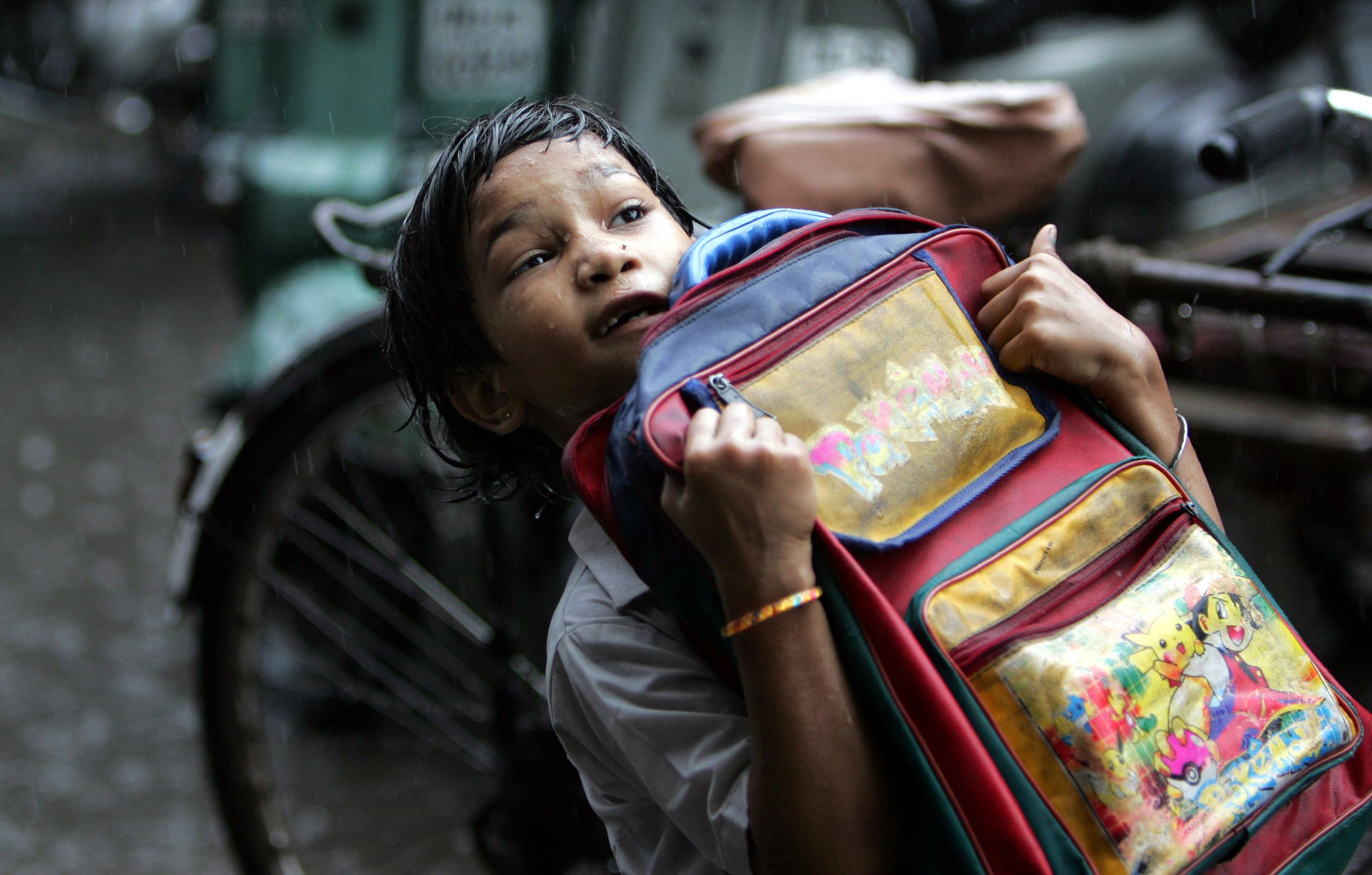 A young student struggles to lift up her school under rains in New Delhi on July 4, 2007. (File photo: AP)
