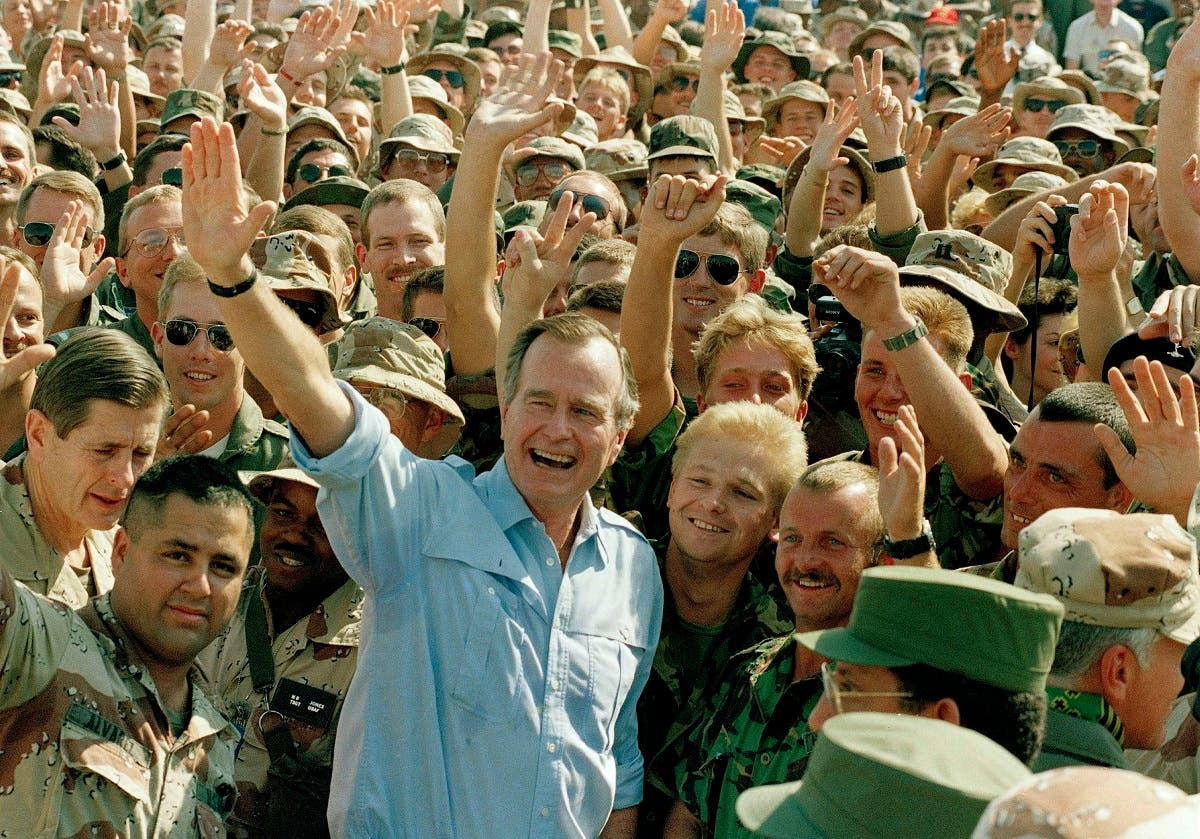 President George Bush poses with soldiers in Dhahran (AP)