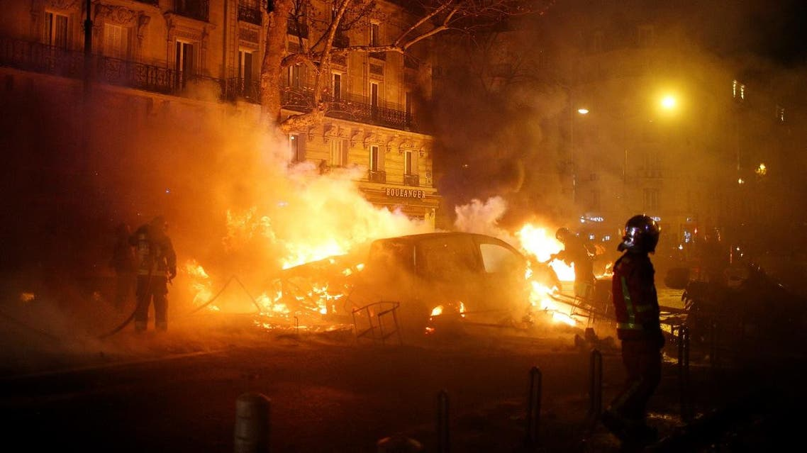 Firemen extinguish burning cars set afire by protesters wearing yellow vests near the Place de l'Etoile in Paris. (Reuters)