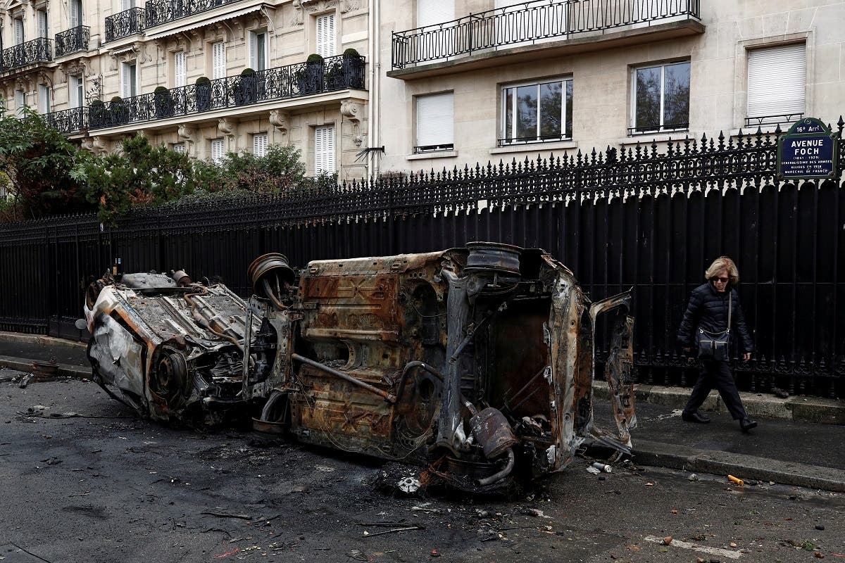 Vandalized cars are seen on a street the morning after clashes with protesters wearing yellow vests, a symbol of a French drivers' protest against higher diesel taxes, in Paris. (Reuters)
