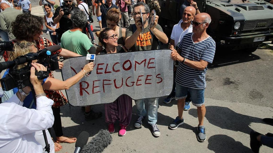 People hold a placard reading Welcom refugees as they protest against the visit of Italy's new hardline interior minister at the reception centre (CPSA) in Pozzallo, Sicil. (AFP)