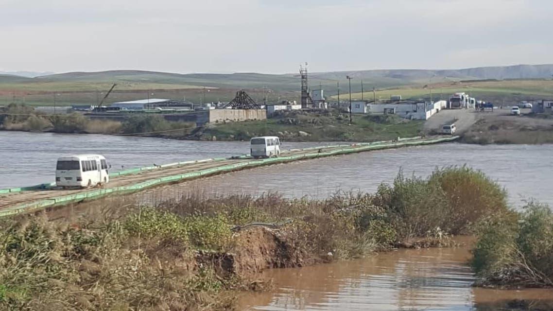 حافلتان فوق جسر مروري يعلو نهر دجلة.