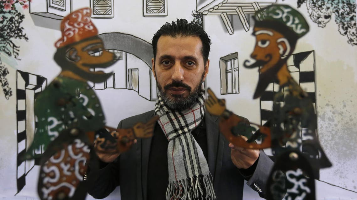 Syrian last shadow puppeteer Shadi al-Hallaq holds his puppets Karakoz (L) and Eiwaz (R) before a presentation in Damascus on December 3, 2018. (AFP)